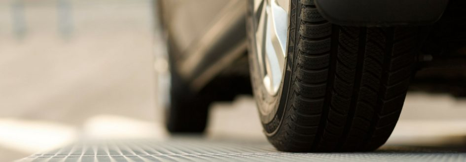 Close up of car tires on pavement featured in a blog about used cars