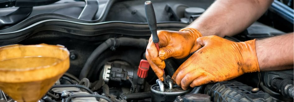 A close-up of a technician working on an engine featured in a blog about used cars