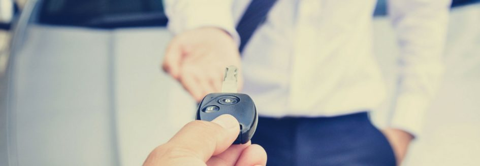 A man being handed a car key featured in a blog about used Toyota Camry models