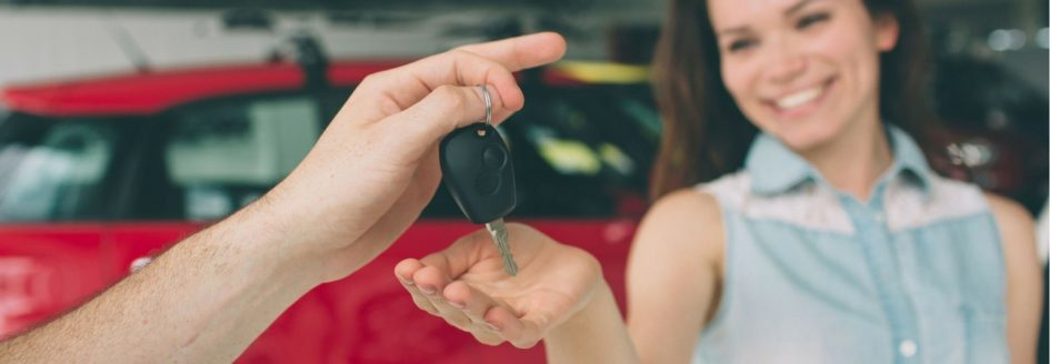 A woman accepting a car key featured in a blog post about used cars