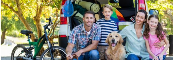 A family with their dog in front of a car featured in a blog post about driving tips
