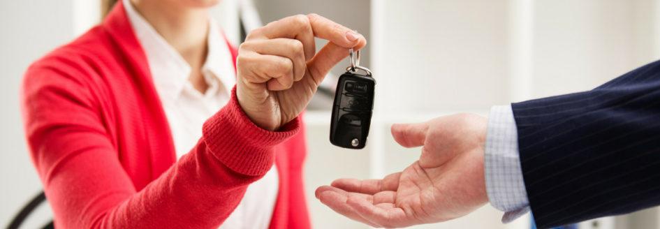 sales associate handing off car key to customer