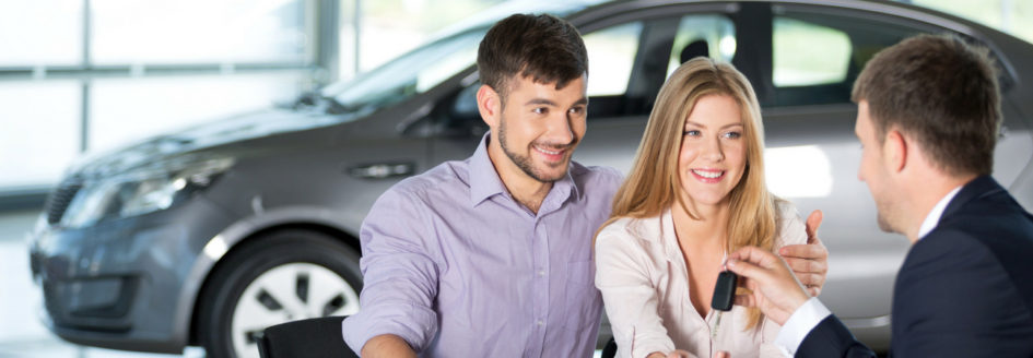 couple buying used car from sales person in dealership showroom
